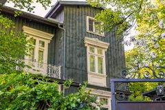 Wooden house real estate. Classical grey Wooden house façade. real estate. American Style with balcony. surrounded by green vegetation. Vienna, Austria Royalty Free Stock Photos