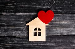 Wooden house with a red heart on a background of black wooden boards. A notification icon for the application. Love nest, love. Relationships. Buying a house stock photos