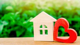 Wooden house and red heart. Concept of sweet home. Property insurance. Family comfort. Affordable housing for young families.