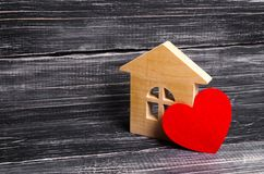 Wooden house with a red heart on a dark wooden background. A house for lovers, a honeymoon. Purchase your own affordable housing. For young families. Planning royalty free stock photo