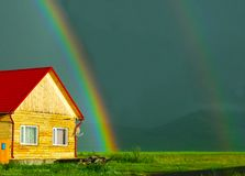 Wooden house with a red roof and rainbow stock photos