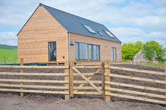 Wooden house in Scotland. Simple wooden house with gate and fence in Scottish countryside location Royalty Free Stock Photo