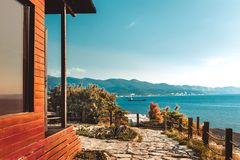 Wooden house by sea and mountain perfect landscape view sunset. Scenery vacation relaxation recreation holiday luxury concept stock image