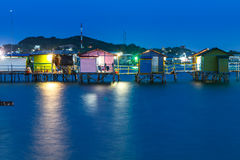 Wooden house on the sea at night with color light Royalty Free Stock Photography