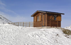 Wooden House in the Snow. Small wooden house on a snowy mountain Stock Image