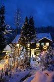 A wooden house in the snow, covered with Christmas lights stock images