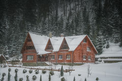 Wooden house. Snow-covered house. Wood and house in winter Stock Photography
