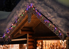 Wooden house in the snow with garlands Royalty Free Stock Photos