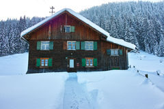 Wooden house in snowy landscape. The traditional architecture of a south-Bavarian farm house in the snow-covered landscape of the alpine upland Royalty Free Stock Image