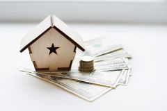 Wooden house stands on a pile of paper bills dollars as a symbol of mortgage on white background. Saving money royalty free stock image