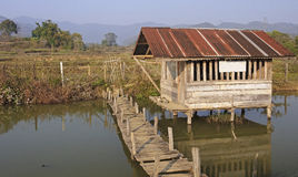 The wooden house on stilts over a pond Royalty Free Stock Photography
