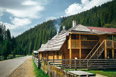 Wooden house surrounded by mountains and green coniferous forest near to the countryside road, summertime. Royalty Free Stock Photography