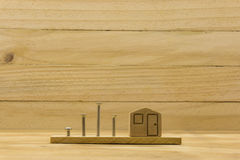 Wooden house symbol. With screw on wood background Stock Images