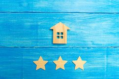 Wooden house and three stars on a blue background. Rating of houses and private property. Buying and selling, renting apartments. The level of the restaurant stock photos
