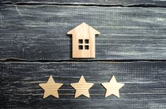 Wooden house and three stars on a gray background. Rating of houses and private property. Buying and selling, renting apartments. The level of the restaurant stock photography