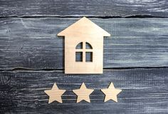 Wooden house and three stars on a gray background. Rating of houses and private property. Buying and selling, renting apartments. The level of the restaurant royalty free stock photo