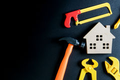 Wooden house toy and construction tools toy on black background stock images