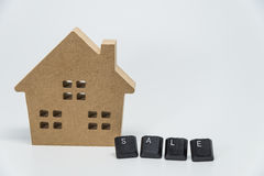 Wooden house toy and SALE word from keyboard with white background and selective focus Royalty Free Stock Image