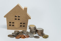 Wooden house toy and Thai baht coin with white background and selective focus Royalty Free Stock Photos