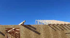 Wooden house under construction. Building of a new neighborhood stock photography