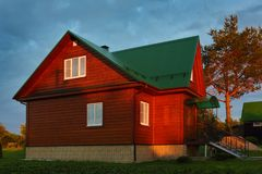 Wooden house under green metal roof sunset lihgts stock photo