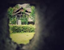Wooden house viewed from a tunnel shaped hole