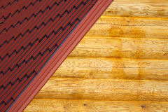 Wooden house wall and part of red roof from metal tile closeup Royalty Free Stock Photo