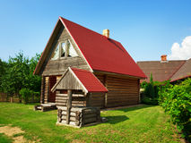 Wooden house and well in the yard Royalty Free Stock Image