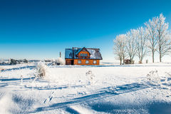 Wooden house in winter. Blue sky and frosty snowy grass field and trees stock photography