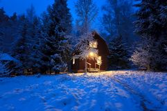 Wooden house in winter forest. Light night windows Royalty Free Stock Photography