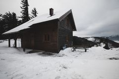 Wooden house in winter forest on a mountain royalty free stock images