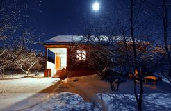 Wooden house in winter forest. night. moonlight. Wooden house in winter forest light night windows royalty free stock images