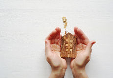 Wooden house in the woman`s hands on a white wooden background. Stock Image