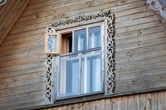 Wooden house with wood frame window in roof ridge Stock Images
