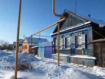 The wooden house and yellow tubes. The blue wooden house and yellow gas tubes in the Russian town stock photo