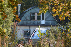 Wooden house among the yellowed trees - autumn rural landscape Royalty Free Stock Photography