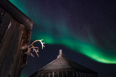 Wooden house, yurt hut on the background the polar Northern aurora borealis lights Royalty Free Stock Photo