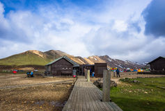 Wooden houses in camping Landmannalaugar, Iceland. Tents stands in camping in mountains at sunny day Stock Photos
