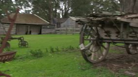 Wooden houses and cart shot. A medium shot of wooden house and cart with trees. Camera pans to the right stock video footage