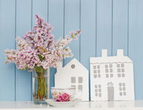 Wooden houses, china teacup and bunch of lilac Royalty Free Stock Images