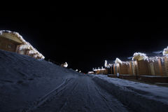 Wooden houses with garlands along the road winter night Royalty Free Stock Photo