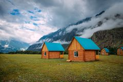 Wooden houses in a green valley on a background of mountains in the fog and cloudy sky, close-up. Tourist base in the Altai. Mountains. Houses near the big rock stock images