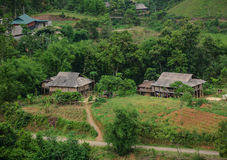 Wooden houses in a Hmong village with mountain background  in Moc Chau Stock Photos