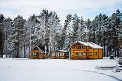 Wooden houses in a nature area covered with snow. Stock Photo