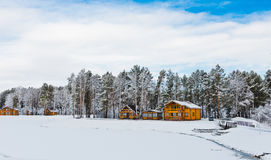 Wooden houses in a nature area covered with snow. Stock Images