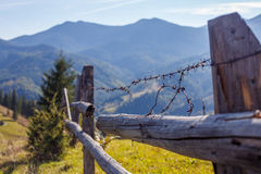 Wooden houses near fence on mountain background. Barbed wire on the wooden fence on mountain backgrond and blue sky background Stock Images