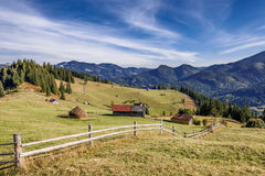 Wooden houses near fence on mountain background Stock Image