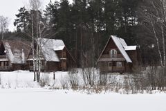 Wooden houses from pine forest winter landscape the lake in the snow Stock Photos