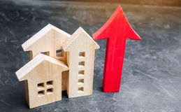 Wooden houses with a red arrow up. concept of high demand for real estate. increase energy efficiency of housing. rise in house. Prices. property. population stock photo