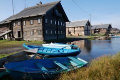 Wooden houses on the shore and  boats in fishing village Royalty Free Stock Photo